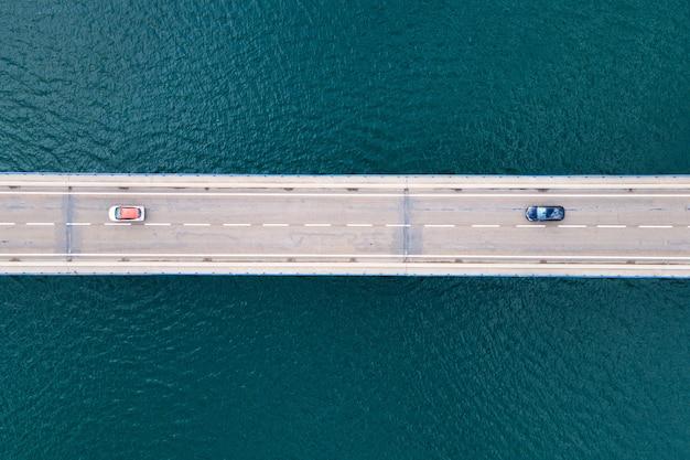 Вид с воздуха на мостовую дорогу с автомобилями над озером или морем.