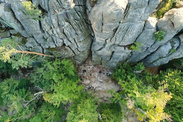 緑の森の木々と夏の密林の間に大きな岩の岩がある明るい風景の空撮。野生の森の美しい風景。
