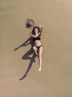 바다 근처 모래에 일광욕하는 갈색 머리 여자의 공중 전망. 그녀는 검은 색 비키니를 입고있다. 그녀는 혼자입니다. 그녀는 웃고있다. 그녀는 손으로 평화의 상징을 만들고 있습니다.