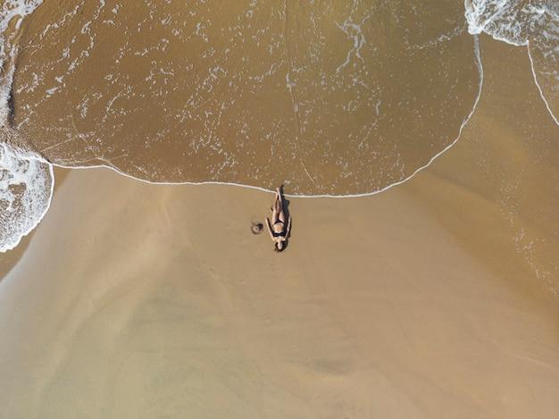 Вид с воздуха на брюнетку, загорающую на песке у моря. на ней черное бикини. она одна.