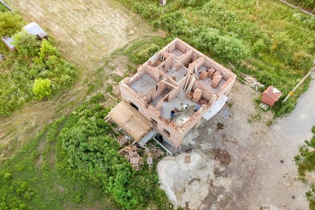 Вид с воздуха на строительную площадку для будущего дома, кирпичный цокольный этаж и стопки кирпича для строительства.
