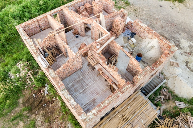 将来の家、レンガの地下階、建設用レンガの山の建設現場の空撮。