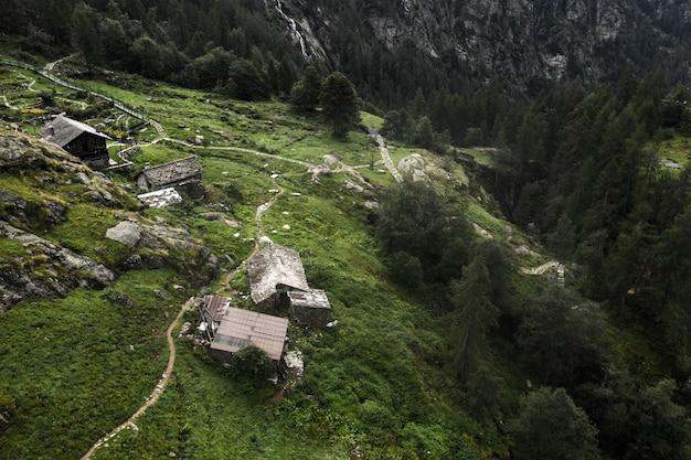 緑の高山に立つ建物の空撮