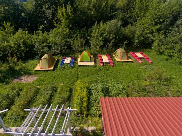 Аэрофотоснимок лагеря туристов с палатками на берегу реки
