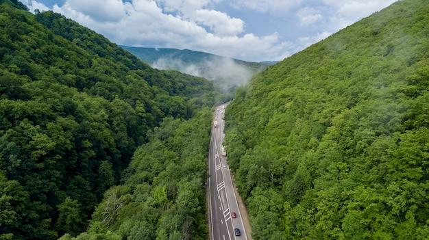 ソチロシアの森を通る曲がりくねった山道に沿って運転している車の空撮