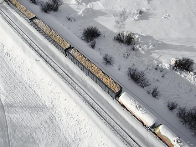 Аэрофотоснимок вагонов-цистерн грузовых поездов на двухпутной железной дороге с белым снегом в зимний вид сверху
