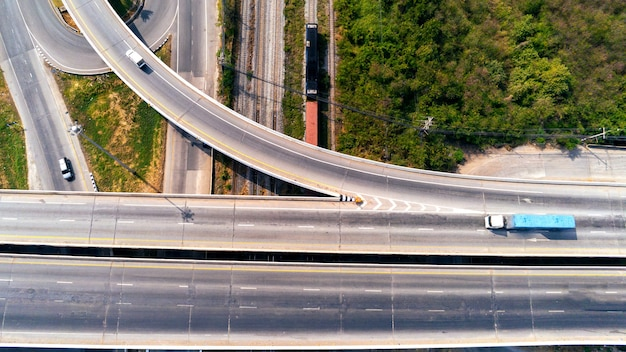 자동차, 운송 개념이 있는 고속도로 도로의 화물 트럭 및 기차 컨테이너의 항공 보기. 아스팔트 고속도로의 수입, 수출 물류 산업 운송