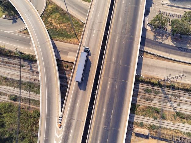 青いコンテナ、輸送コンセプト、輸出入ロジスティック産業輸送アスファルト高速道路の陸上輸送で高速道路上の貨物トラックの航空写真