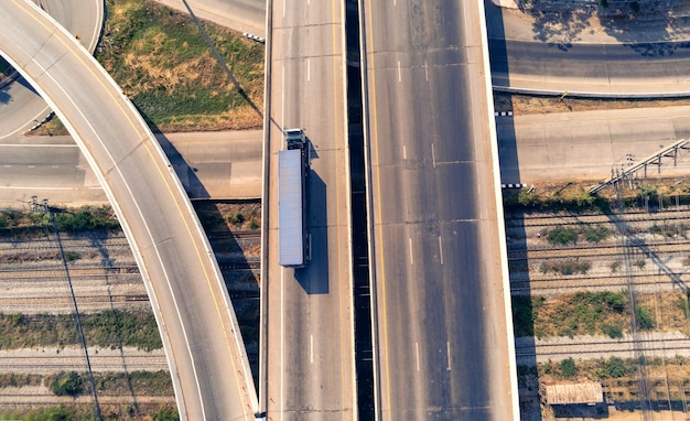 Вид с воздуха на грузовой автомобиль на шоссе с синим контейнером, транспортная концепция., импорт, экспорт, логистика, промышленная транспортировка, наземный транспорт на асфальтовой скоростной дороге