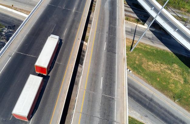 컨테이너, 운송 개념이 있는 고속도로에서 화물 흰색 트럭의 항공 보기. 수입, 수출 물류 산업 수송 아스팔트 고속도로에서 육상 운송
