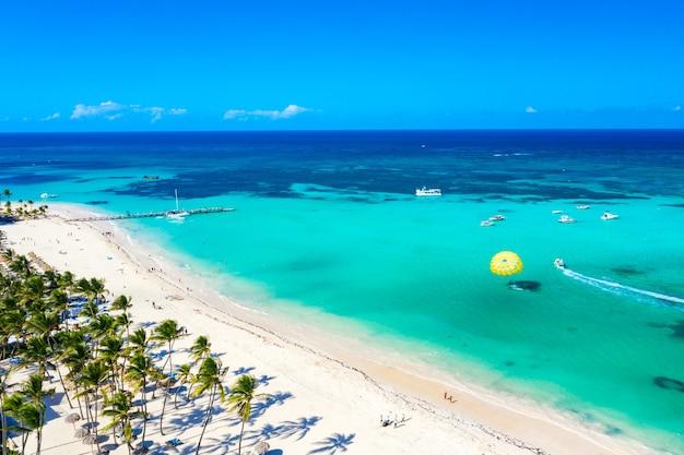 Вид с воздуха на тропический пляж карибского бассейна с соломенными зонтиками, пальмами и лодками