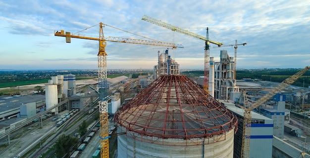 工業生産地域で高コンクリートプラント構造とタワークレーンを備えた建設中のセメント工場の航空写真。製造とグローバル産業の概念。