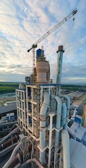산업 생산 현장에서 높은 콘크리트 공장 구조와 타워 크레인이 있는 시멘트 공장의 공중 전망. 제조 및 글로벌 산업 개념입니다.