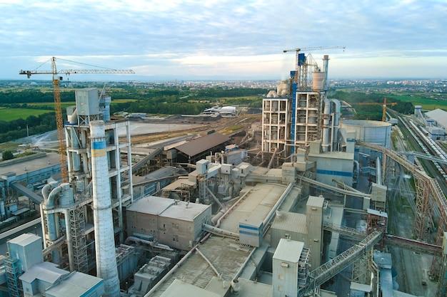 Вид с воздуха на цементный завод с высокой структурой бетонного завода и башенным краном на промышленной производственной площадке. производство и глобальная отраслевая концепция.