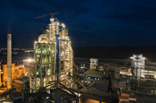 밤에 산업 생산 지역에 높은 콘크리트 공장 구조와 타워 크레인이 있는 시멘트 공장의 공중 전망. 제조 및 글로벌 산업 개념입니다.
