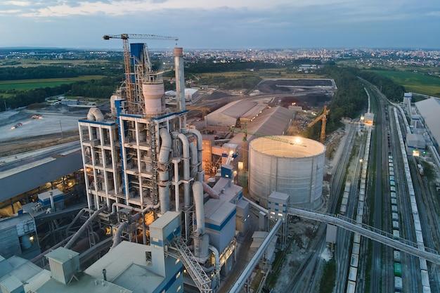 夜の工業生産地域での高コンクリートプラント構造とタワークレーンを備えたセメント工場の航空写真。製造とグローバル産業の概念。