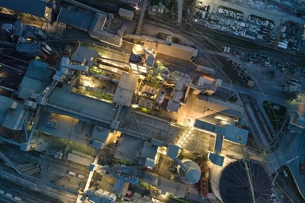 Вид с воздуха на цементный завод с высокой структурой бетонного завода и башенными кранами в производственной зоне в ночное время. производство и глобальная отраслевая концепция.