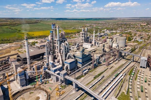 高コンクリート構造のセメント工場と工業生産地域のタワークレーンの航空写真。製造とグローバル産業の概念。