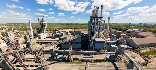工業生産地域の高コンクリート構造とタワークレーンを備えたセメント工場の航空写真。製造とグローバル産業の概念。