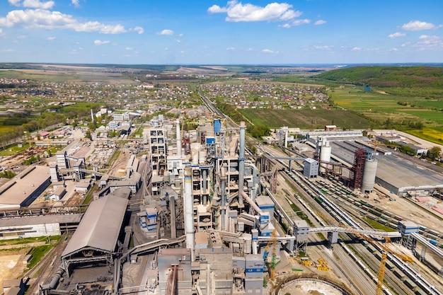 산업 생산 지역에 높은 콘크리트 공장 구조와 타워 크레인이 있는 시멘트 공장의 공중 전망. 제조 및 글로벌 산업 개념입니다.
