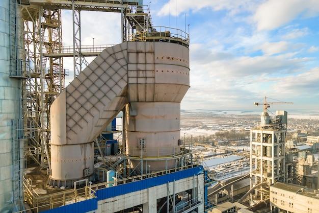 일몰에 산업 생산 지역에서 높은 공장 구조와 타워 크레인 시멘트 공장의 공중보기.