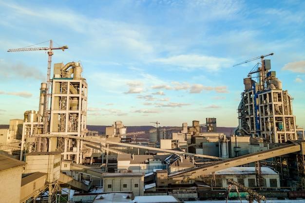 일몰 시 산업 생산 지역에서 높은 공장 구조와 타워 크레인이 있는 시멘트 공장의 공중 전망.