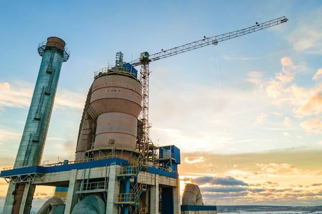 日没時の工業生産地域での高い工場構造とタワークレーンを備えたセメント工場の航空写真。