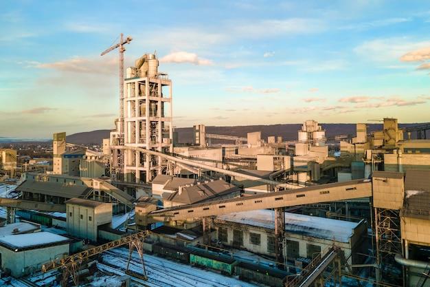 산업 생산 지역에 높은 공장 구조와 타워 크레인이 있는 시멘트 공장의 공중 전망.