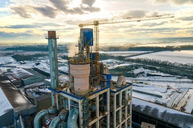 Вид с воздуха на цементный завод с высокой структурой завода и башенным краном на промышленной производственной площадке.