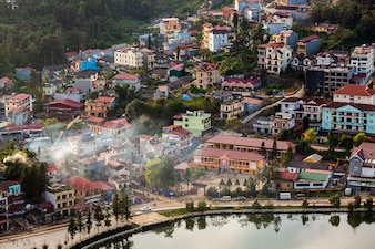 Aerial view of clusters of buildings nestled in the green valley of Sapa, Vietnam