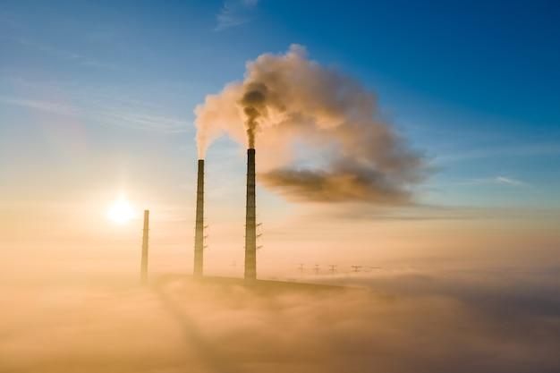 日没時に汚染された雰囲気を上昇する黒い煙のある石炭火力発電所のハイパイプの航空写真。
