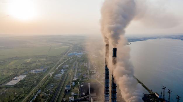 Вид с воздуха на высокие трубы угольной электростанции с черным дымом, движущимся вверх по загрязняющей атмосфере на закате.