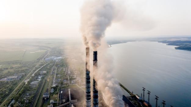 Вид с воздуха на высокие трубы угольной электростанции с черным дымом, движущимся вверх, загрязняя атмосферу на закате.