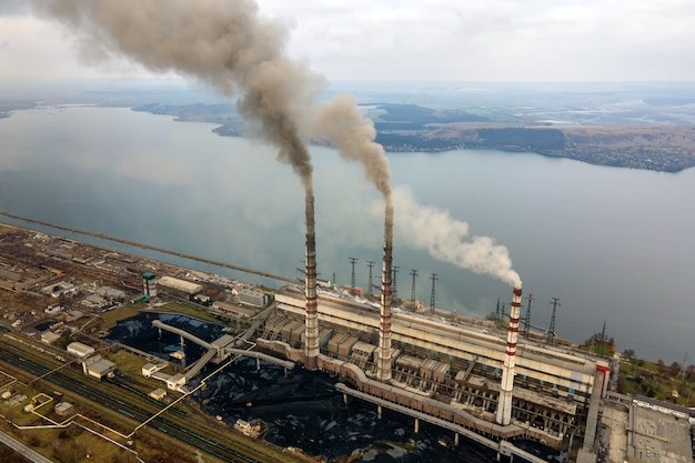 Вид с воздуха на высокие трубы угольной электростанции с черным дымом, движущимся вверх по загрязняющей атмосфере.