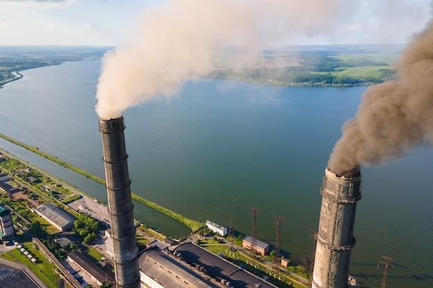 Вид с воздуха на высокие трубы угольной электростанции с черной дымовой трубой, загрязняющей атмосферу. производство электроэнергии с использованием концепции ископаемого топлива.