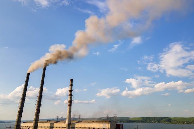 Вид с воздуха на высокие трубы угольной электростанции с черной дымовой трубой, загрязняющей атмосферу. производство электроэнергии с использованием ископаемого топлива.