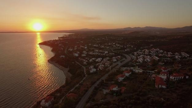 Вид с воздуха на прибрежный курортный городок с коттеджами на берегу моря в греции