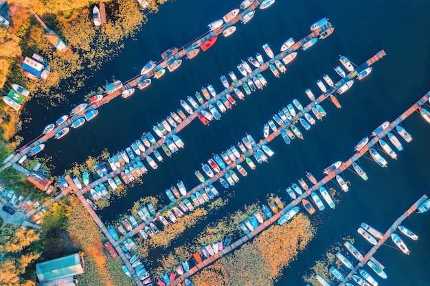 여름에 해질녘 바다에 있는 다채로운 보트와 요트의 공중 전망. 부두, 모터보트, 요트, 노란 수련, 푸른 물이 있는 호수가 있는 풍경. 항구의 상위 뷰입니다. 수송