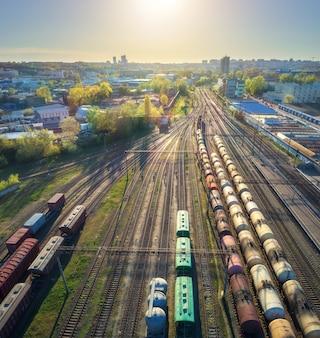 夕暮れ時の駅のカラフルな貨物列車の空撮。鉄道の商品とワゴン。重工業。貨物列車、都市の建物、青い空と産業シーン。ドローンからのトップビュー