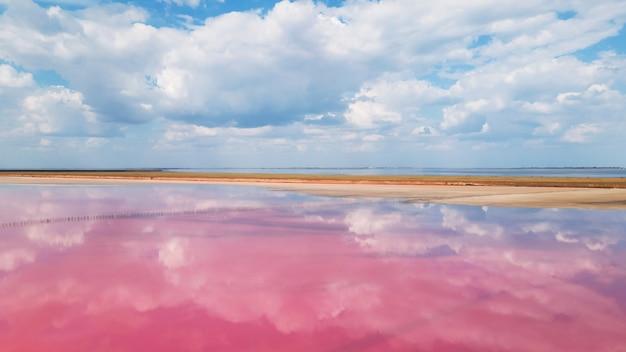 Вид с воздуха на красочное розовое соленое озеро и отражение облаков. геническ, украина