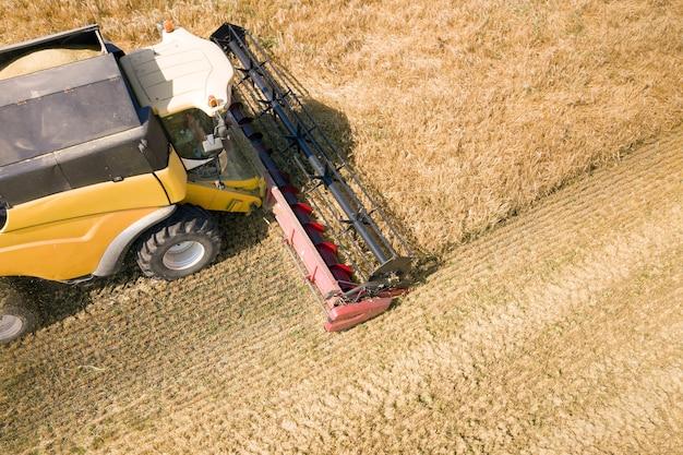 Вид с воздуха на зерноуборочный комбайн, собирающий большое поле спелой пшеницы. сельское хозяйство с точки зрения дрона.