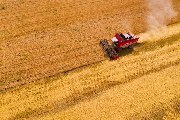 Аэрофотоснимок комбайна, собирающего спелую пшеницу на поле