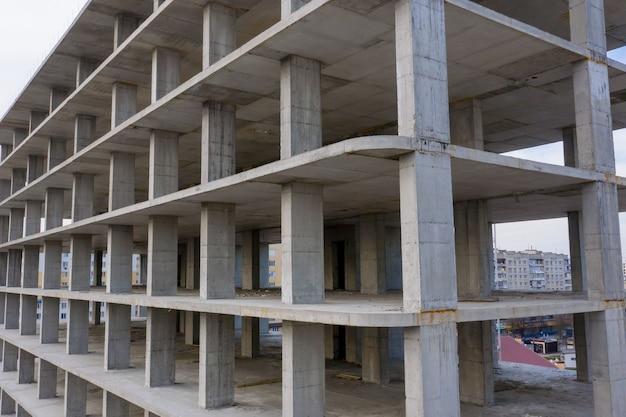Вид с воздуха на бетонный каркас строящегося многоэтажного жилого дома в городе.