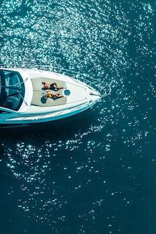 海を移動する豪華ヨットで日光浴を楽しんでいるカップルの空撮