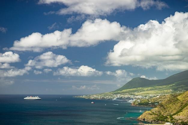 緑の山々とカリブ海の島の近くのクルーズ船の空撮。
