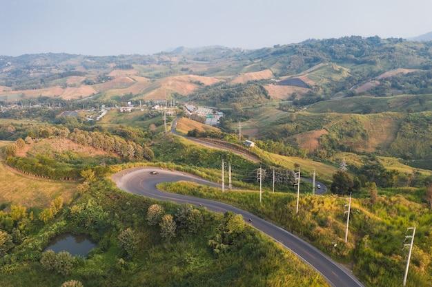 田園地帯の緑の丘に電柱のある湾曲したアスファルト道路の空撮
