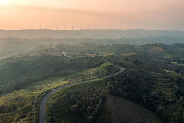 녹색 언덕에 있는 곡선 고속도로의 공중 전망과 시골의 일몰 피크에 풍력 터빈. 깨끗하고 재생 가능한 에너지 개념