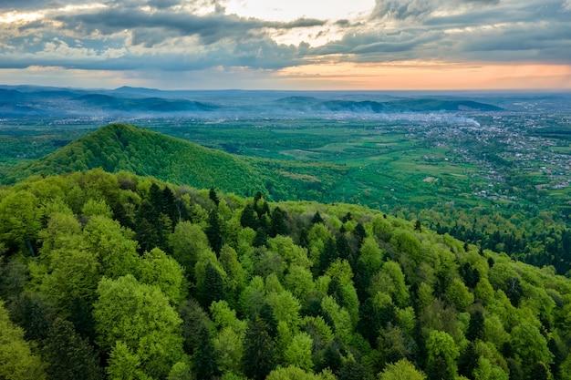 夕方には緑の混合松と緑豊かな森に覆われた暗い山の丘の空撮。