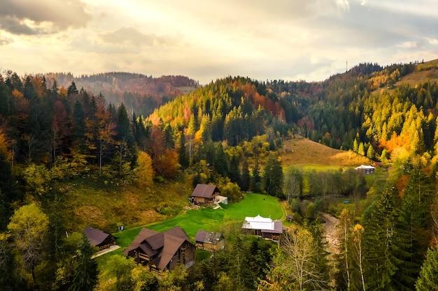 Аэрофотоснимок далекой деревни с небольшими пастушьими домиками на широких холмах луг между осенними лесными деревьями в украинских карпатах на закате.