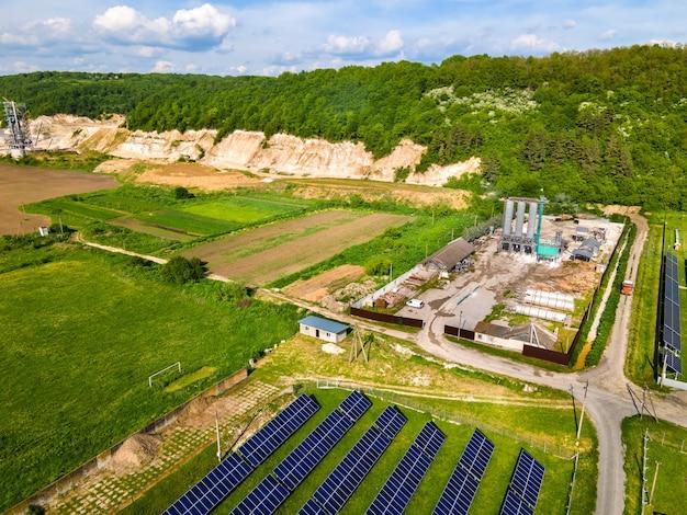 산업 지역에서 깨끗한 생태 전기 에너지를 생산하기 위한 태양광 패널이 줄지어 있는 발전소의 공중 전망. 제로 배출 개념의 재생 가능한 전기.